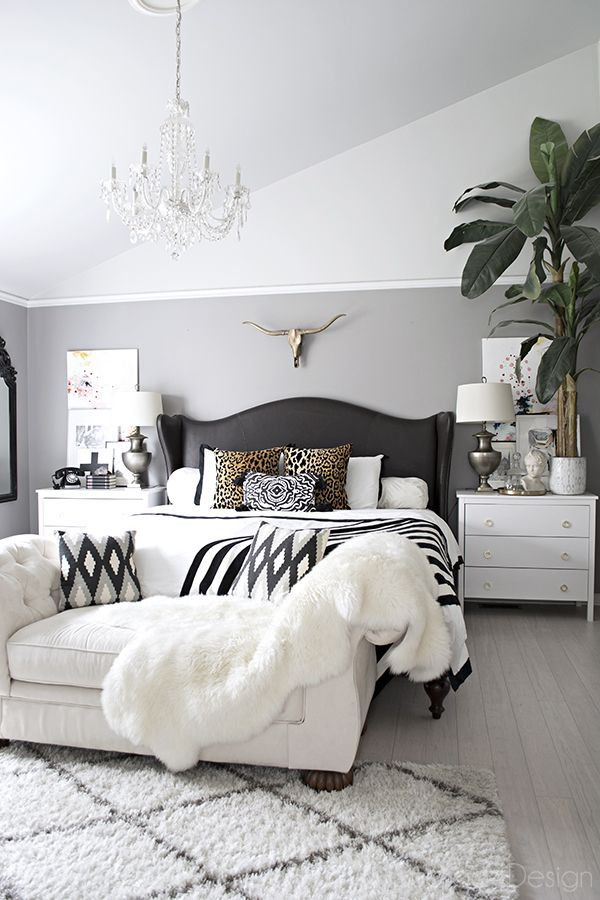Attractive black and white headboard neutral bedroom with crystal chandelier, button tufted chaise, black and  white accents rfhqnpz